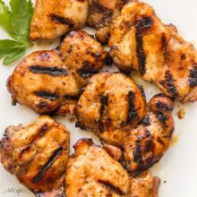 square image of grilled boneless chicken thighs on white plate
