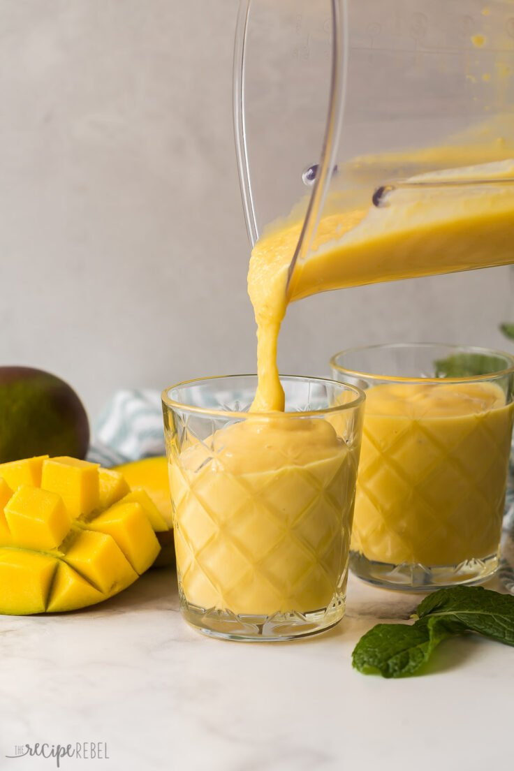 pouring mango smoothie into glass from blender