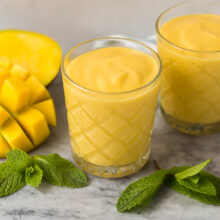 two mango smoothies in glasses with fresh mango and fresh mint