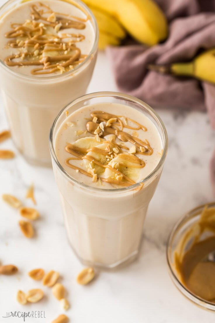 close up image of peanut butter banana smoothie with sliced bananas and peanut butter drizzle