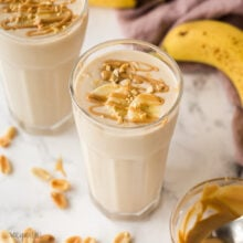 close up image of peanut butter banana smoothie in glass