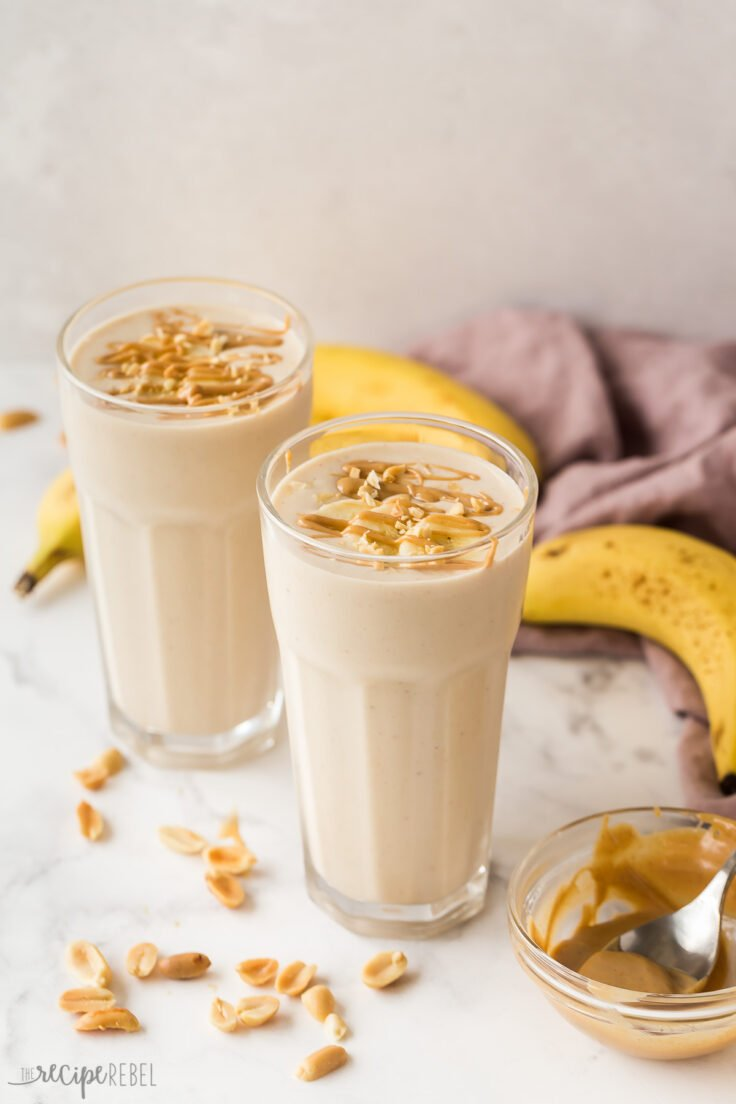 two glasses of peanut butter banana smoothie on white background