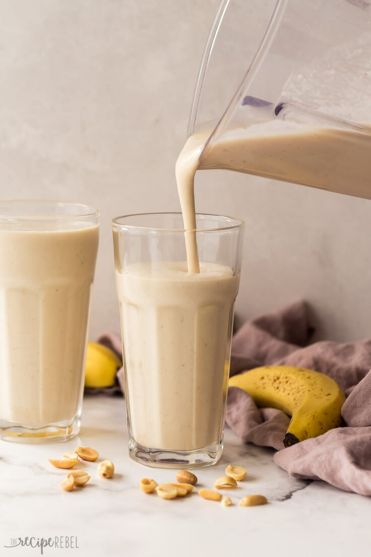 pouring peanut butter banana smoothie into glasses from blender