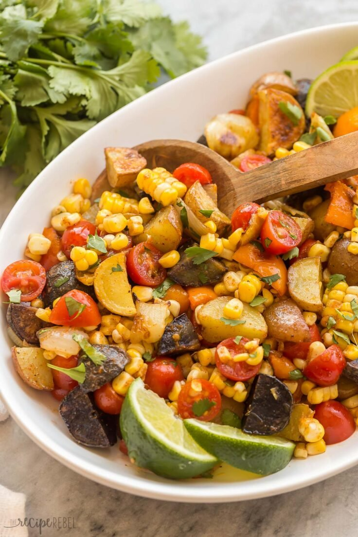 close up image of mexican potato salad with wooden spoon and lime wedges