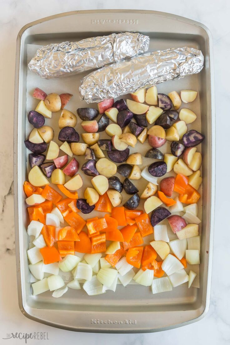 corn wrapped in foil and other vegetables on sheet pan for roasting
