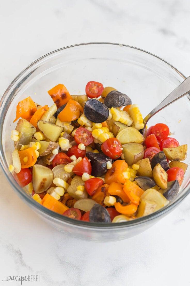 roasted vegetables stirred together in glass bowl