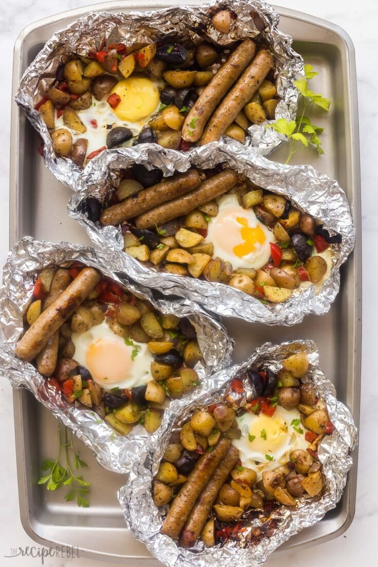 four foil pack breakfasts lined up on sheet pan