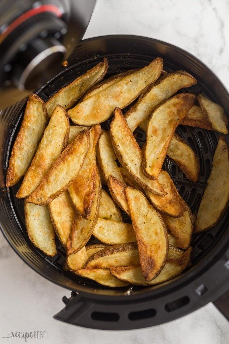 overhead image of air fryer potato wedges in air fryer basket