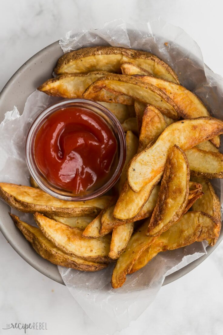 bowl of crispy potato wedges with small bowl of ketchup