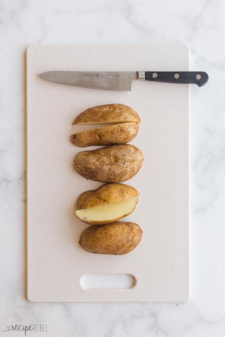 cutting russet potatoes in quarters on cutting board