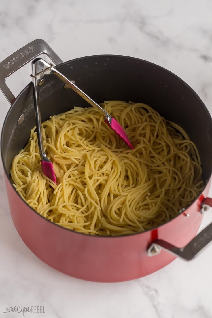 cooked spaghetti in large pot with tongs