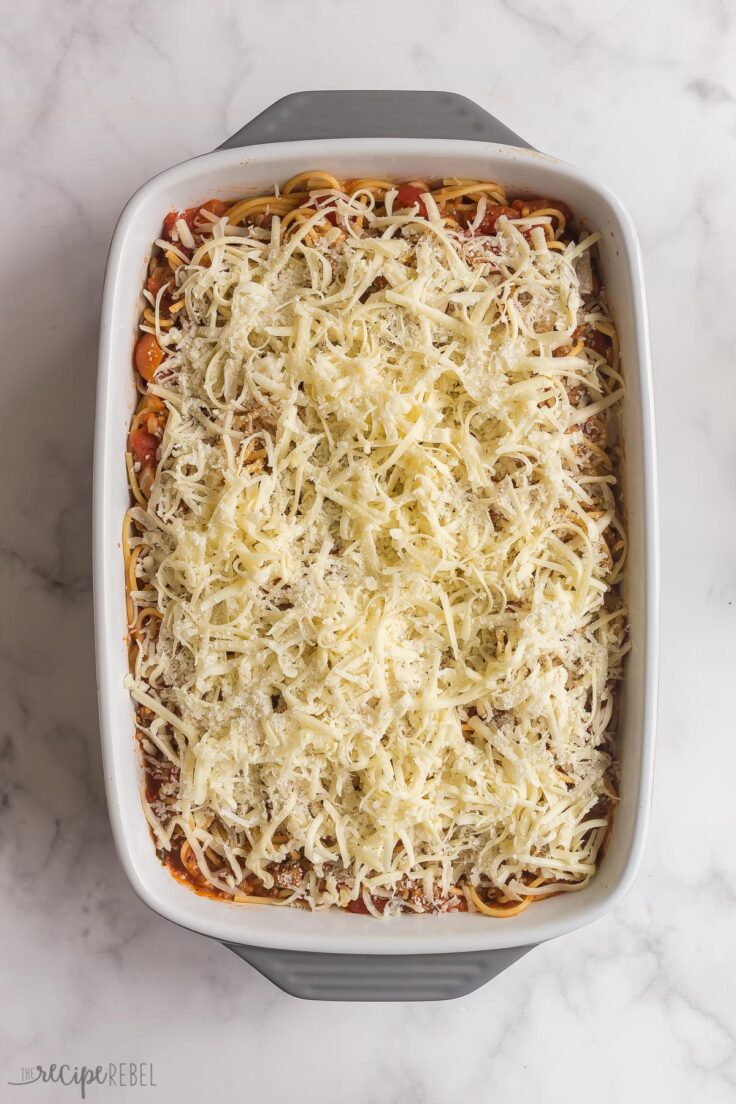 baked spaghetti in baking dish with cheese on top before baking