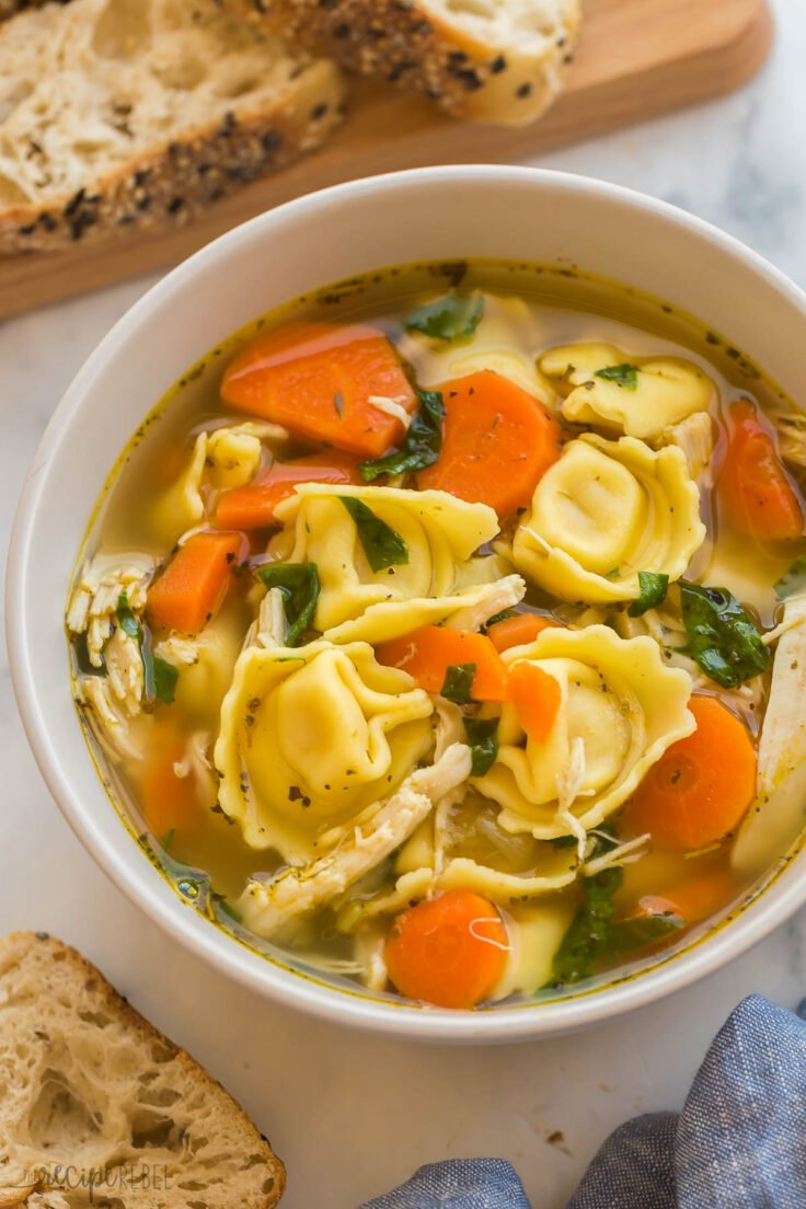 close up image of chicken tortellini soup in beige bowl