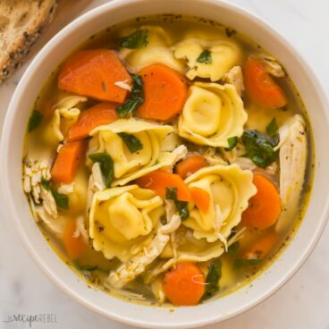 square image of chicken tortellini soup in beige bowl