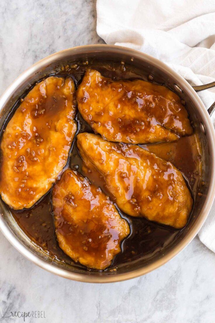 four chicken breasts in a skillet with honey garlic sauce