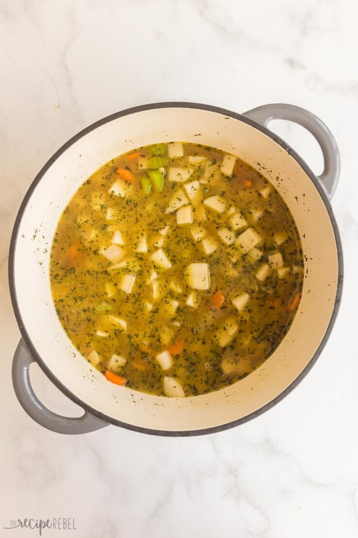 potatoes and broth added to vegetables in soup pot