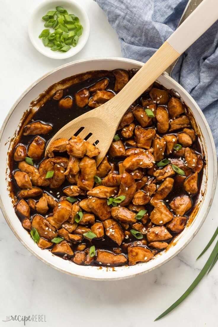 overhead image of teriyaki chicken in skillet with wooden spoon