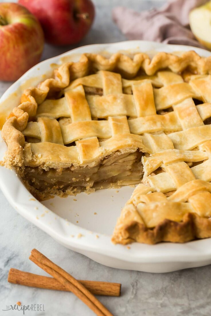 whole apple pie in plate with piece missing