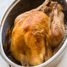 whole roast turkey in roasting pan with golden skin