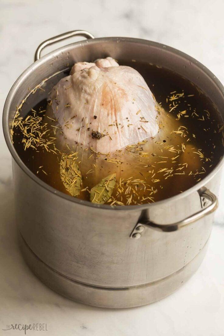 raw turkey being submerged in turkey brine