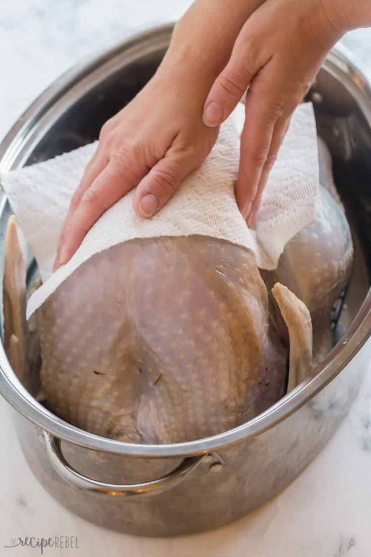 paper towels being used to pay turkey dry after brine